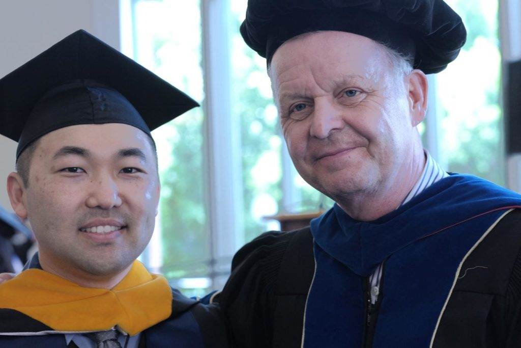"alt=""Data Analytics Graduate student Tim and Dr Hans at the 2017 Graduation in commencement attire"""